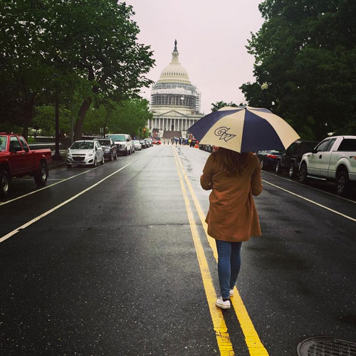 A student carries a 广发娱乐广发娱乐首页 umbrella in front of the Capitol